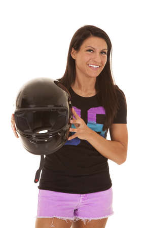 A woman with a smile on her face holding on her motorbike helmet. photo