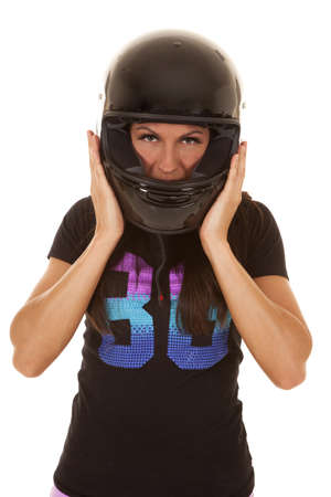 A woman with her hands on her helmet getting ready to take it off. photo