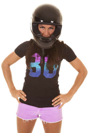 A woman standing with her hands on her hips wearing her helmet. photo