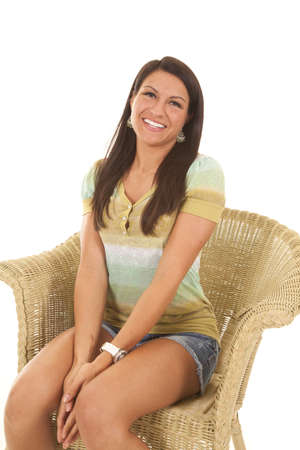 a woman sitting in a wicker chair with a smile on her face. photo