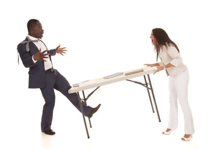 A woman angry with her business partner throwing a table at him. photo