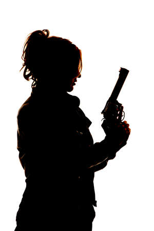 A silhouette of a woman  holding on to her pistol. photo