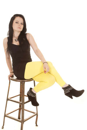 A woman in yellow pants sitting on a stool serious. photo