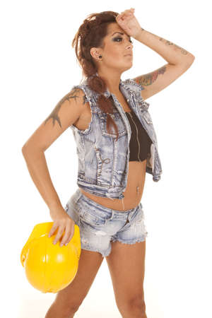 A woman in denim with a yellow hard hat and tattoos. photo