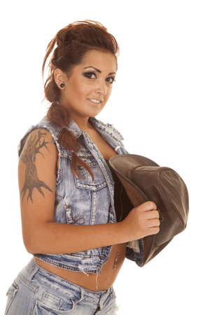 A woman in denim with tattoos holding a western hat Stock Photo - 21687429