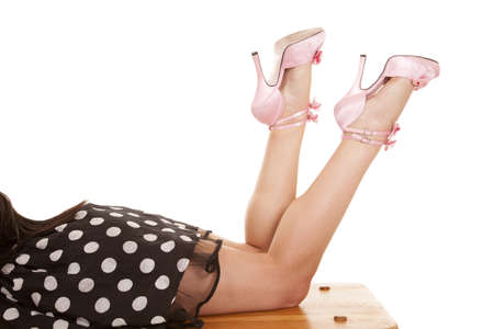 a woman laying on a bench in her polka dot dress and pink shoes photo