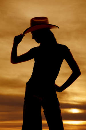 A silhouette of a woman touching the brim of her hat. photo