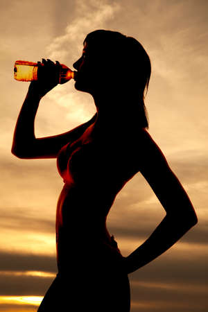 A silhouette of a woman drinking water. photo