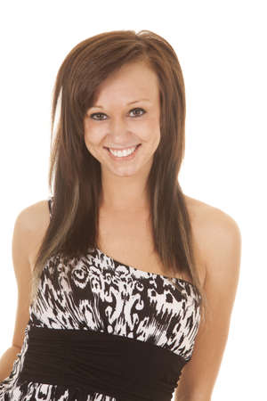 A woman with a smile on her face in her black and white dress on.