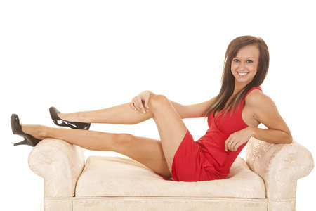 A woman with a smile on her face sitting on a white bench in her red dress smile. Stock Photo - 21680884