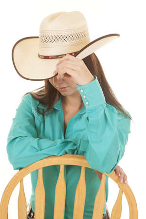 A woman sitting on a chair holding on to her brim of her cowgirl hat. photo