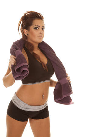 A woman with tattoos workout with a towel around shoulder. photo