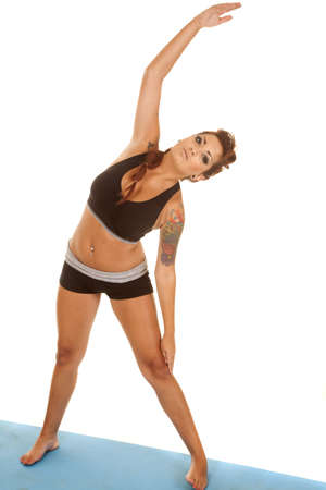 A woman in workout clothes with tattoos stretching. photo