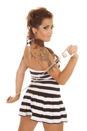 jailbird: A woman with a tattoo and handcuffs in her hands. Stock Photo