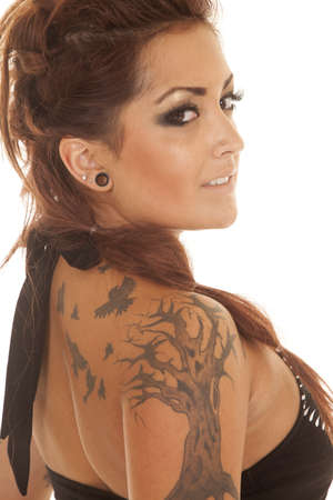 A woman in a black tank top with a tattoo of a tree and birds. photo