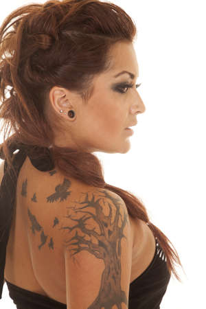 A woman in a black tank with tattoos from the side. photo