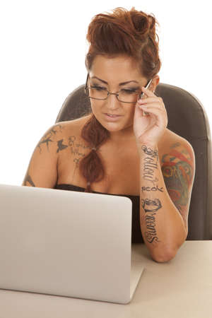 A woman with tattoos looking down at a computer. photo