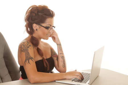 A woman with tattoos sitting at a laptop working.