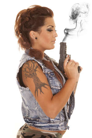 A woman with a gun and tattoos and smoke. photo