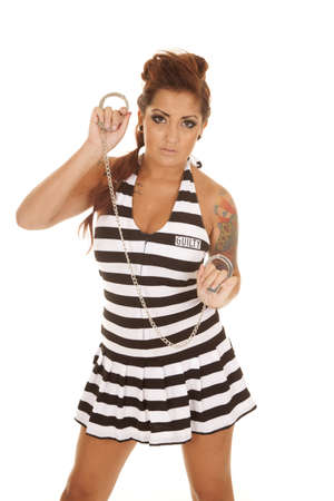 inmate: A woman with handcuffs in her hands and tattoos. Stock Photo