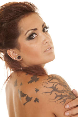A woman up close with tattoos on shoulder. photo