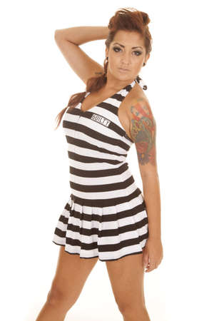 A woman with tattoos in a jail outfit.