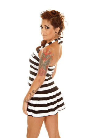 convict: A woman in a jail outfit with tattoos from the back.