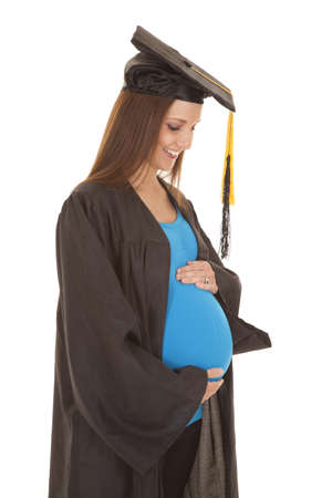 A pregnant woman in a graduation gown holding her belly. photo