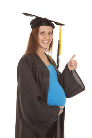 A pregnant woman in a graduation gown giving a thumbs up. photo