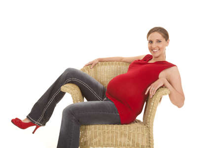 A pregnant woman sitting in a chair smiling. photo