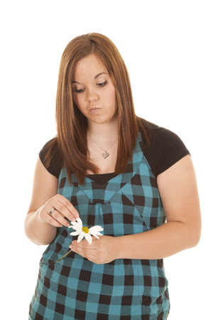 a woman with a silly face picking the petals off of her flower photo
