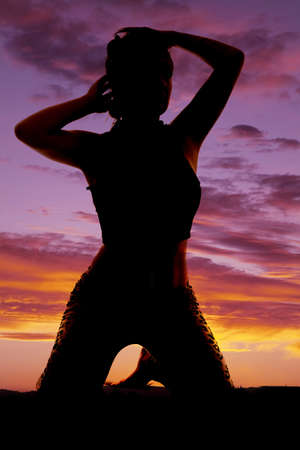 A silhouette of a woman on her knees with her hands by her hair.