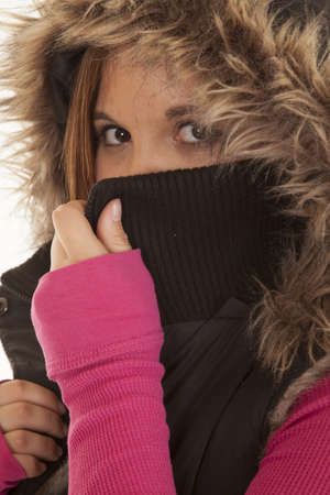 a woman covering her mouth with her jacket. photo