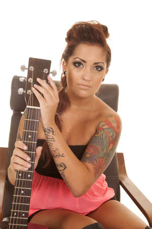a woman with a serious expression on her face holding on to her guitar. photo