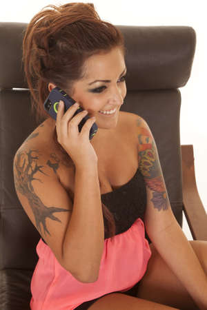 tatoos: A woman with tatoos sitting in a chair talking on a cell phone.