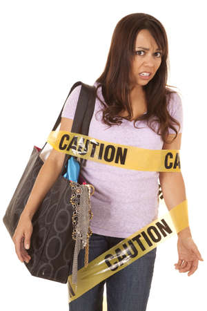 A woman with an upset expression wrapped in caution tape and holding a purse full of stuff. photo