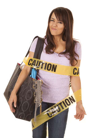 A woman with a bag full of stuff with a funny expression on her face wrapped in caution tape. photo