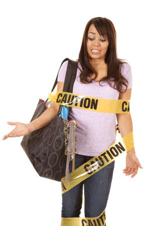 hazard tape: A woman wrapped up in caution tape with her purse full of stuff.
