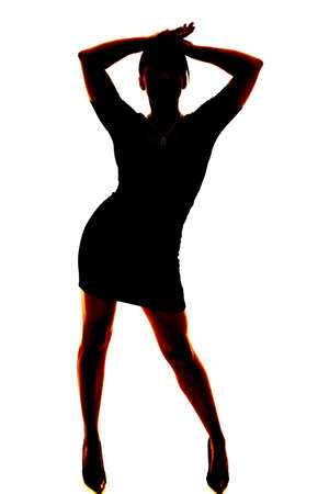A silhouette of a woman dancing in her skirt and heels. photo