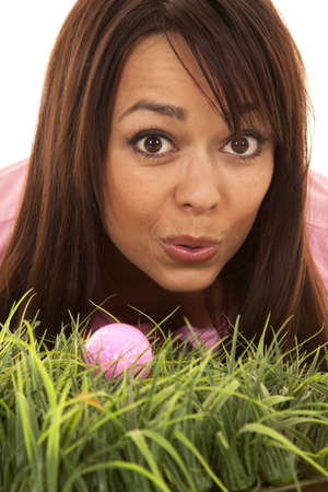 A close up of a woman trying to blow her golf ball in, in the deep tall grass.