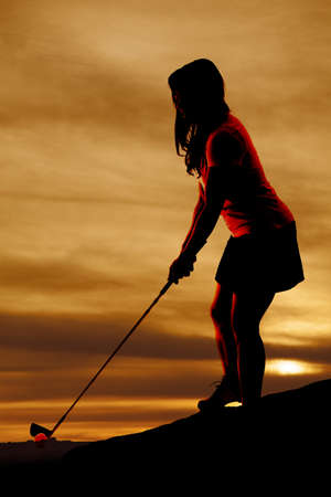 A silhouette of a woman golfing, with a beautiful sky behind her. photo