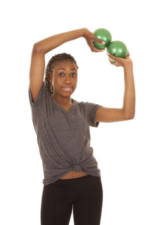 weighted: A woman working out with weighted green balls with a funny expression.