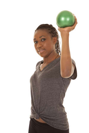 weighted: a woman working out with her weighted green balls .