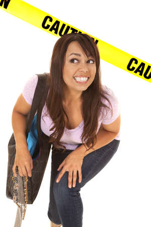 agachado: una mujer con una expresión divertida pasando por debajo de la cinta de precaución. Foto de archivo