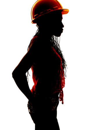 a silhouette of a woman in her construction helmet. photo