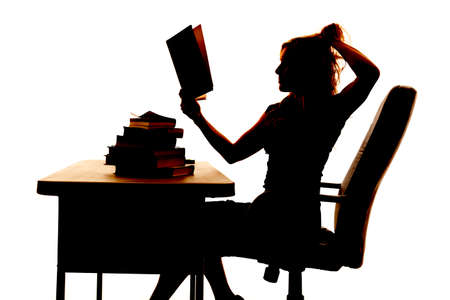 a silhouette of a woman at her desk with a stack of books reading and wanting to pull her hair out. photo