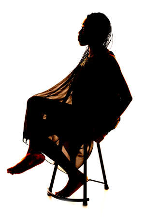 a silhouette of a woman sitting in a chair in her lacy dress. photo