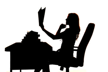 A silhouette of a woman thinking and holding her book up. Stock Photo