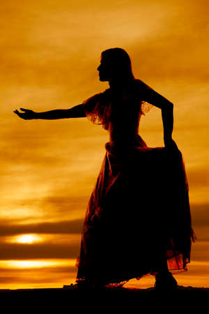 a silhouette of a woman in her dress with her hand reaching out .