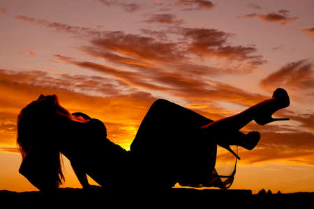 A silhouette of a woman laying back in her fitted dress and heels. 免版税图像